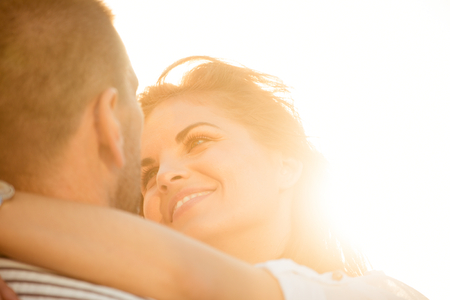 lovers embracing: Happy couple having great time together - photographed at sunset against sun Stock Photo