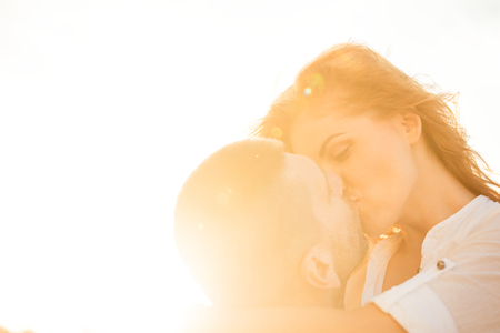 against the sun: Couple kissing at sunset - photographed against sun Stock Photo