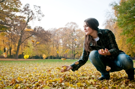 healthy llifestyle: Happy life - woman throwing leaves in fall Stock Photo