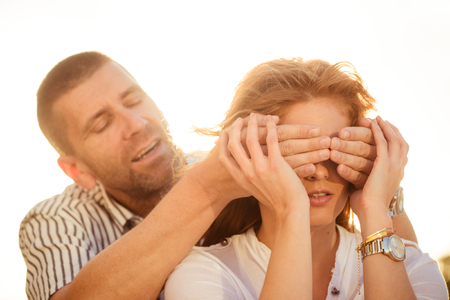 hand covering eye: Who is it - Man surprises woman