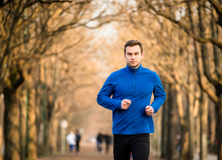 and the horizontal man: Man jogging in early spring nature Stock Photo