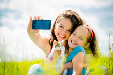 taking: Selfie - mother, child and kitten Stock Photo