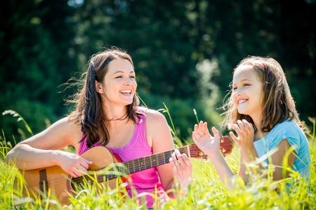 niño cantando: Madre que toca la guitarra en la naturaleza Foto de archivo