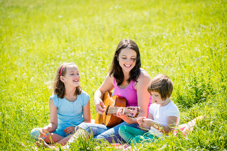 Mother playing guitar in nature to children