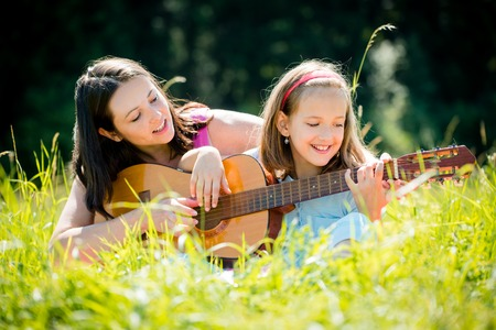 parent child: Mother teaching daughter playing guitar Stock Photo