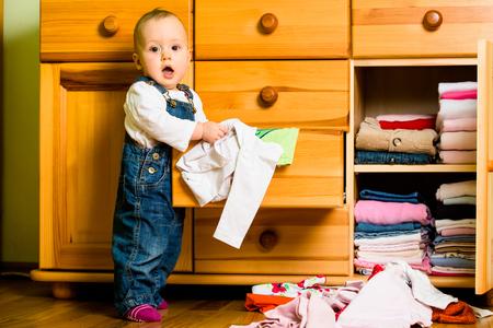 habitacion desordenada: Las labores dom�sticas - beb� echa la ropa Foto de archivo