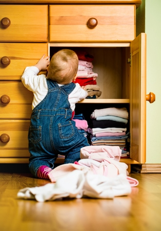 messy clothes: Domestic chores - baby throws out clothes