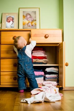 habitacion desordenada: Las labores domésticas - bebé echa la ropa Foto de archivo