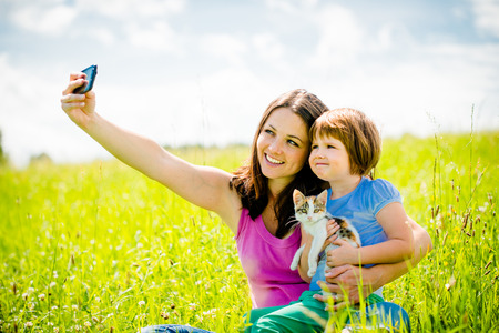 taking photograph: Selfie - mother, child and kitten Stock Photo