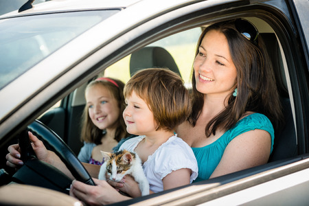 woman driving car: Mother and child driving car Stock Photo