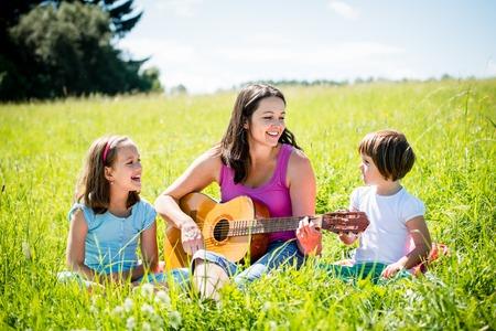 persona cantando: Madre tocando la guitarra en la naturaleza para niños Foto de archivo