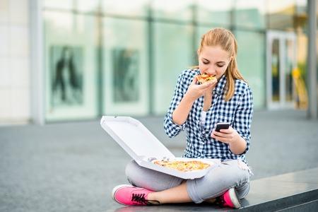 Adolescente comiendo pizza mirando en el teléfono