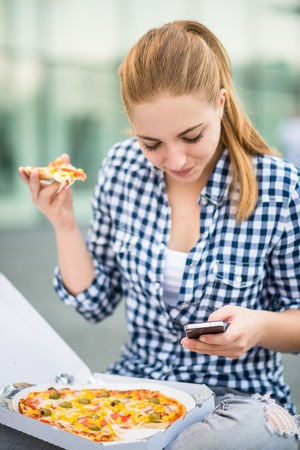 Teenager eating pizza looking in phone photo