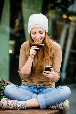 Teenager eating muffin looking in phone photo