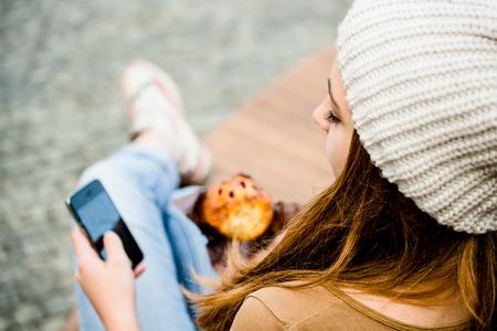 Adolescente panecillo de alimentación, buscando en el teléfono