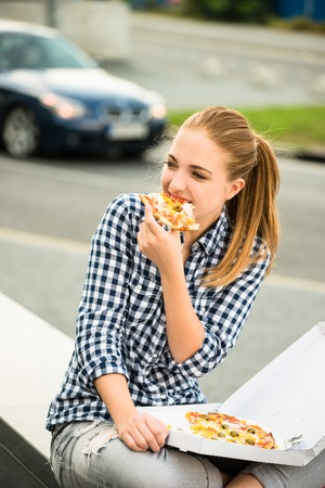 Teenager eating pizza in street photo