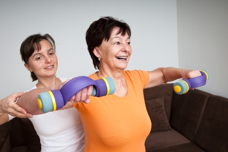 senior exercise: Coach assisting senior woman exercising