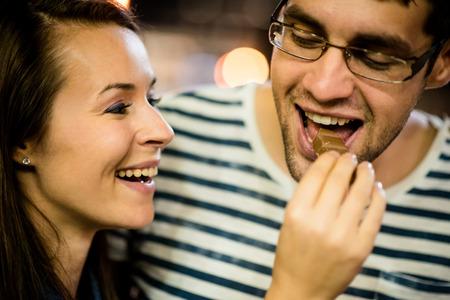 dattes: Couple de manger du chocolat à la date de nuit Banque d'images