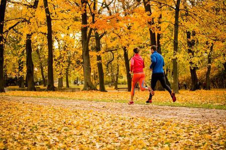 man    health: Couple jogging in autumn nature Stock Photo