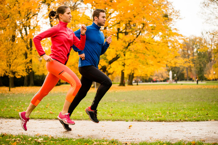 from side: Couple jogging in autumn nature Stock Photo