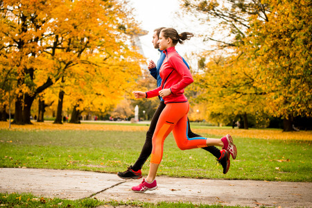 parks: Couple jogging in autumn nature Stock Photo
