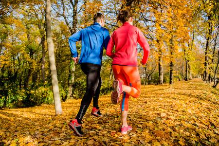 秋の自然の中ジョギング カップル 写真素材