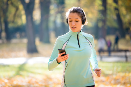 checking: Woman jogging and listening music Stock Photo