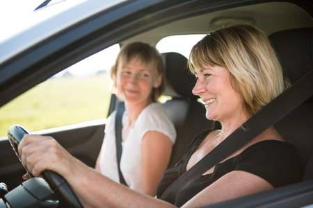woman driving car: Mature woman with daughter driving car