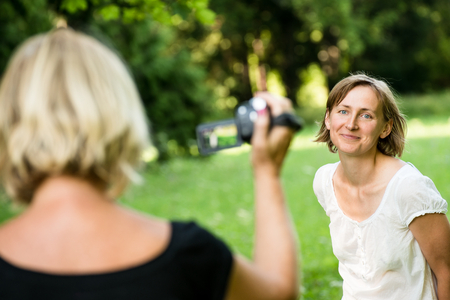taking video: Senior mother is taking video of her adult daughter in nature with camcorder Stock Photo