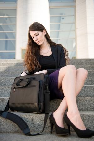 Mujer de negocios que buscan en la bolsa de ordenador portátil