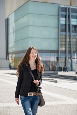Young woman with laptop bag walking on street photo