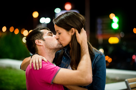 young couple hugging kissing: Couple kissing at night Stock Photo