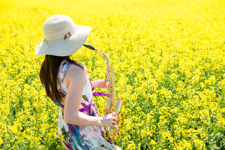 saxophonist: Young  saxophonist (woman) playing saxophone in blossoming rapeseed field