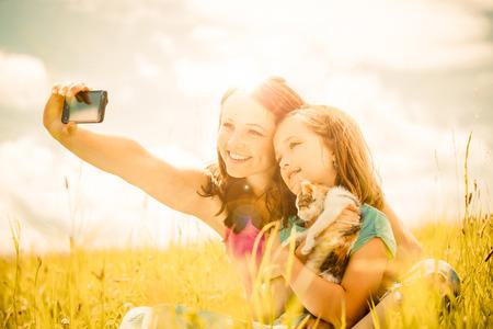 Selfie - mother, child and kitten Standard-Bild