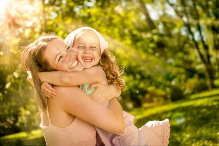 Happy mother hugging with her child in nature on sunny day - photo with flare photo