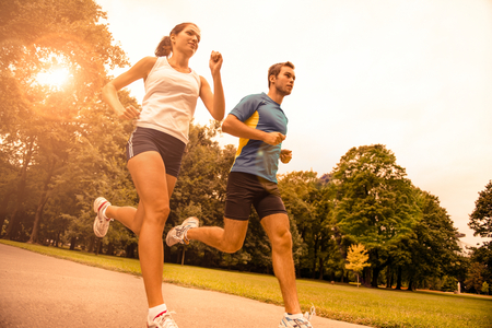 Low angle photo of young couple  jogging outdoor in park