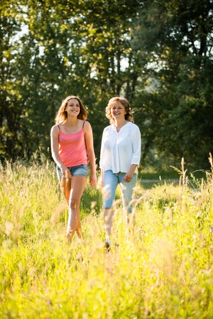 mother and teen daughter: Mature woman and her teenage daughter walking together outdoor in nature on sunny summer day Stock Photo