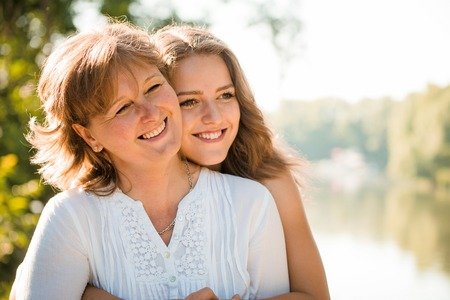 madre e hija adolescente: Madre madura con su hija adolescente que mira en una dirección - a contraluz con el sol