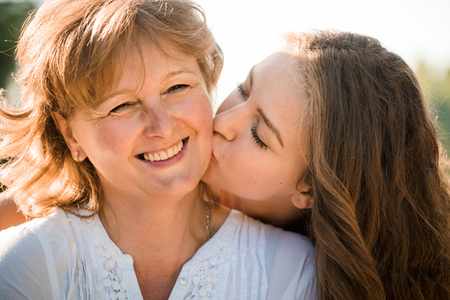 Close up of teenage girl hugging and kissing her mother h outdoor in nature on sunny day Banque d'images