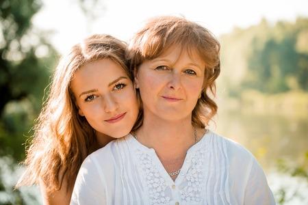 madre e hija adolescente: Retrato al aire libre de la madre madura con su hija adolescente - a contraluz con el sol