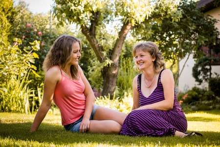 talk: Mature woman chatting with her teenage daughter outdoor in nature