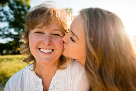 mother and teen daughter: Teenage daughter kissing her mother outdoor in nature with sun in background, wide angle Stock Photo