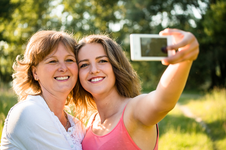 Adult daughter and her senior mother are taking selfie photo with mobile phone Stock Photo