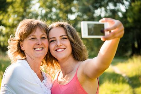 madre e hija adolescente: Hija adulta y su madre de alto nivel est�n tomando la foto selfie con el tel�fono m�vil Foto de archivo