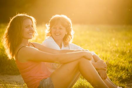 padres hablando con hijos: Adolescente que habla con su madre sentada en la hierba en la naturaleza, la llamarada del sol poniente en la foto
