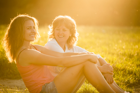 padres hablando con hijos: Teenage girl talking with her mother sitting on grass in nature, flare from setting sun in photo