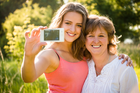 Teenage daughter and her senior mother are taking selfie photo with mobile phone