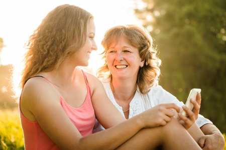 Teenage girl showing her mother photos on mobile phone outdoor in nature with setting sun in background Imagens