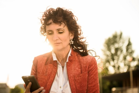 mobile phones: Serious senior woman in red jacket looking to her mobile phone while sitting in street at sunset