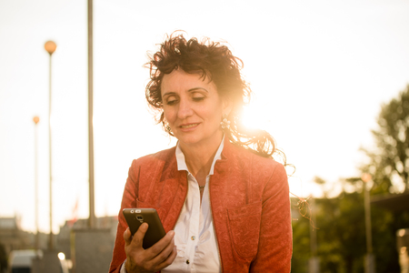 people   lifestyle: Senior woman in red jacket looking to her mobile phone while sitting in street at sunset